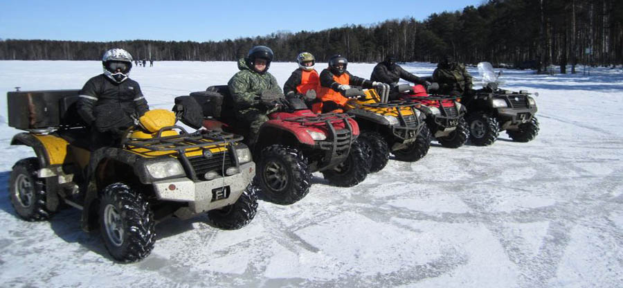 парни на квадроцикле на замерзшем ледяном озере зимой